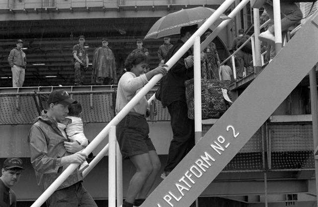 U.S. military personnel and dependents board the nuclear-powered aircraft carrier USS ABRAHAM LINCOLN (CVN 72) during evacuation of Clark Air Base and Naval Station, Subic Bay. Evacuees are being transported from the area in the aftermath of the eruption of Mount Pinatubo, a volcano that came alive on June 10th for the first time in over 600 years