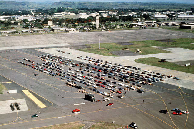 Vehicles line an airfield in preparation for shipment as military and civlian personnel and dependents evacuate the area during Operation Fiery Vigil. The evacuation has been prompted by the eruption of Mount Pinatubo, which came to life for the first time in over 600 years. Over 20,000 evacuees are being removed from Clark and Naval Station, Subic Bay, because of the eruption