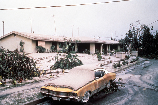 Volcanic ash blankets a home and automobile in the base housing area in the aftermath of the eruption of Mount Pinatubo. More than 20,000 evacuees have been removed from the area as a part of the U.S. military's Operation Fiery Vigil when more than four inches of fallen ash disrupted operations at Clark and Naval Station, Subic Bay