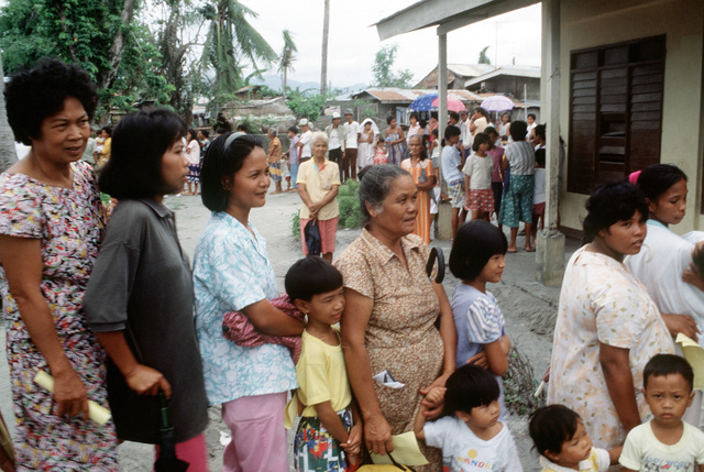 Women and children stand in line to visit the 3rd Tactical Fighter Wing's medical civic action program (MEDCAP) team at the Santa Rosa School. The school is being used as a clinic for more than 1,300 evacuees who have fled the mudslides and flooding caused by heavy rains that fell following the eruption of Mount Pinatubo