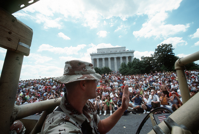 A Marine waves to the crowd gathered near the Lincoln Memorial as he drives a vehicle in the National Victory Celebration parade. The day-long celebration is being held in honor of the coalition forces that liberated Kuwait during Operation Desert Storm