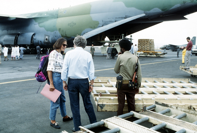 A member of a rebel faction controlling the area listens as Red Cross workers coordinate delivery of supplies for the country's refugees. Meals-ready-eat (MREs) are being unloaded from a Military Airlift Command C-5A Galaxy aircraft and loaded aboard Red Cross vehicles for distribution to those suffering due to the country's civil unrest. The MREs are excess military supplies and are made available by authority of the McCallum Program and the DOD Excess Property Program