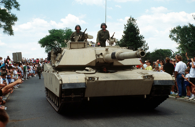 A U.S. Army M-1A1 Abrams tank rolls along a road during the National Victory Celebration parade. The day-long celebration is being held in honor of the coalition forces that liberated Kuwait during Operation Desert Storm