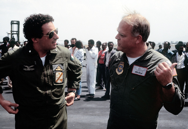 MAJ Gregory Doten, 22nd Military Airlift Squadon, discusses airlift operations with an Italian pilot after transporting a shipment of meals-ready-to-eat (MREs) by C-5A Galaxy aircraft. The supplies will be delivered to the Red Cross for distribution to refugees suffering due to Ethiopia's civil unrest. The MREs are excess military supplies and are made available by authority of the McCallum Program and the DOD Excess Property Program