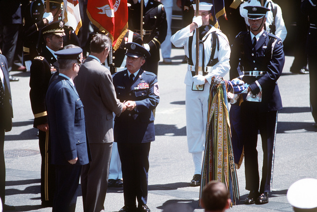 President George Bush greeting CHIEF MASTER SGT. of the Air Force, Gary Phingston, at the campaign streamer ceremony held before the National Victory Celebration parade in honor of the coalition forces from Desert Storm