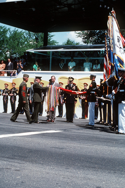 President George H. W. Bush watches as GEN. Alfred M. Gray, commandant of the Marine Corps, attaches a battle streamer to the Marine Corps flag during the National Victory Celebration which is being held in honor of the Allied forces' liberation of Kuwait during Operation Desert Storm