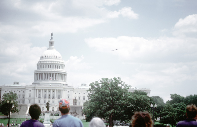 Spectators gather to watch F-117 aircraft fly over the U.S. Capitol prior to the start of the National Victory Celebration which is being held in honor of Allied forces' liberation of Kuwait during Operation Desert Storm