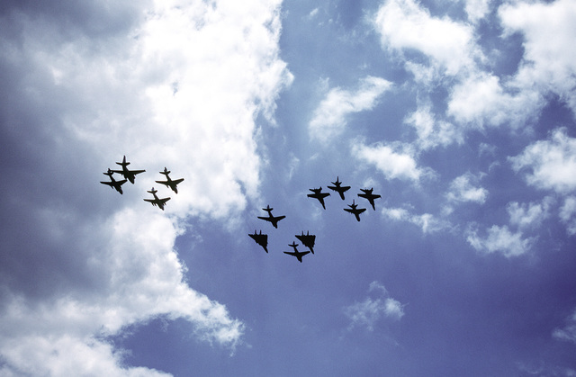 Various aircraft take part in a flyover are silhouetted against the sky during the National Victory Celebration which is being held in honor of Allied forces' liberation of Kuwait during Operation Desert Storm. The plane include, from left: A-6E Intruder aircraft and an S-3A Viking aircraft; at center, F-14A Tomcat and A-6E Intruder aircraft; and A-7E Corsair II aircraft flying with F/A-18 Hornet aircraft at right