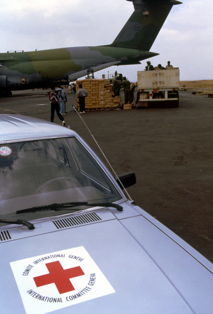 With another Red Cross vehicle parked in the foreground, workers load meals-ready-to-eat (MREs) onto the organization's truck after unloading them from a Military Airlift Command C-5A Galaxy aircraft. The Red Cross will distribute the supplies to refugees suffering due to their country's civil unrest. The MREs are excess military supplies and are made available by authority of the McCallum Program and the DOD Excess Property Program