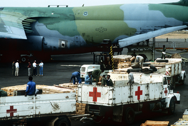 Workers load boxes containing meals-ready-to-eat (MREs) onto a Red Cross truck after the supplies were delivered to Ethiopia by Military Airlift Command C-5A Galaxy aircraft. The Red Cross will deliver the MREs to refugees suffering due to Ethiopia's civil unrest. The MREs are excess military supplies and are made available by authority of the McCallum Program and the DOD Excess Property Program
