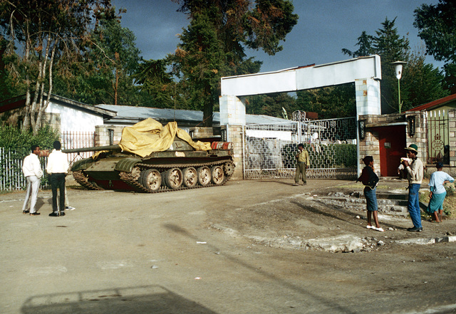 Local residents gather outside the Presidential Palace near a tank abandoned following a battle between rebel forces and the government