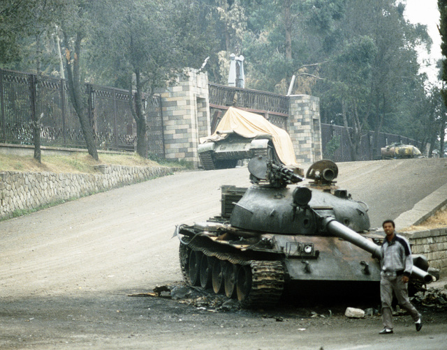Local residents walk past a T-55 main battle tank stranded outside the Presidential Palace following a battle between rebel forces and the government