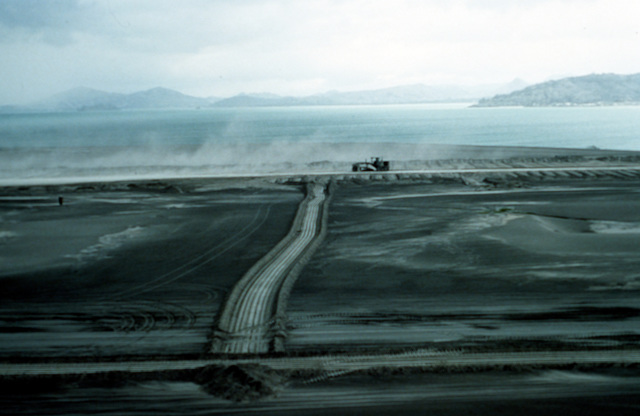A road grader clears ash from the runway at Cubi Point Naval Air Station in the aftermath of Mount Pinatubo's eruption. The volcano, which erupted for the first time in over 600 years, forced the U.S. military to coordinate Operation Fiery Vigil evacuation efforts to remove more than 20,000 evacuees from the area