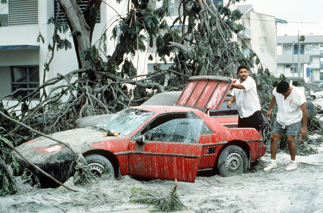 Sailors prepare to dig their car out from under ash and tree limbs in the aftermath of Mount Pinatubo's eruption. The volcano, which erupted for the first time in over 600 years, forced the U.S. military to coordinate Operations Fiery Vigil evacuation efforts to remove more than 20,000 evacuees from the area