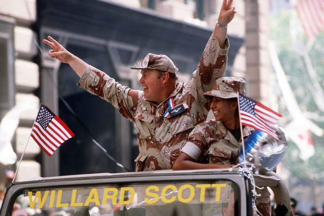 Television personality Willard Scott, wearing camouflage fatigues, stands in an open vehicle waving the the crowd with the sign of victory in the Welcome Home parade honoring the men and women who served in Desert Storm