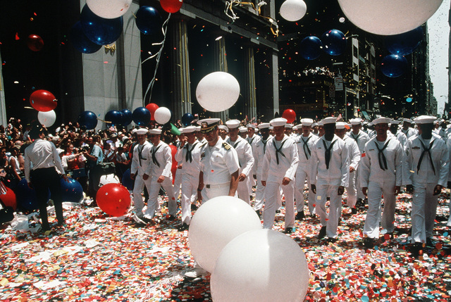 U.S. sailors march along a confetti-covered street as they take part in a ticker tape parade welcoming U.S. military personnel home from deployment in the Persian Gulf area during Operations Desert Shield/Desert Storm