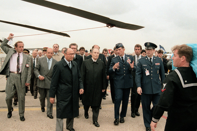 French President Francois Mitterrand, center, is accompanied by a U.S. Air Force general as he tours the American displays at the 1991 Paris Air Show.