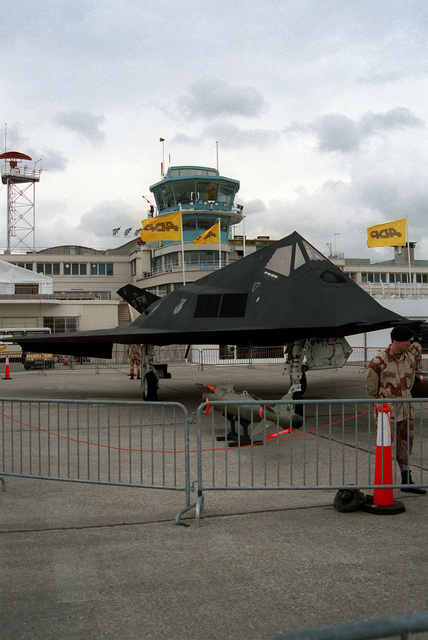 U.S. Air Force security police guard a 37th Tactical Fighter Wing F-117A aircraft on display at the 1991 Paris Air Show. A Paveway II laser-guided bomb is on a pedestal in front of the aircraft.