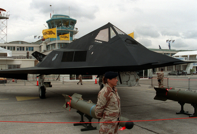 U.S. Air Force security police stand at parade rest around a 37th Tactical Fighter Wing F-117A aircraft on display at the 1991 Paris Air Show. Two Paveway II laser-guided bombs are in front of the aircraft.