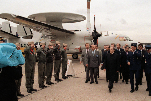 U.S. Navy personnel salute as French President Francois Mitterrand, third from right, and a U.S. Air Force general pass by during their tour of the American displays at the 1991 Paris Air Show. A Carrier Airborne Early Warning Squadron 122 (VAW-122) E-2C Hawkeye aircraft is in the background.