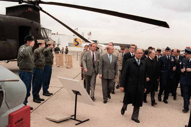 U.S. Navy personnel salute as French President Francois Mitterrand, third from right, and a U.S. Air Force general pass by during their tour of the American displays at the 1991 Paris Air Show.