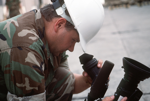 A combat cameraman checks equipment prior to documenting redeployment operations in the aftermath of Operation Desert Storm