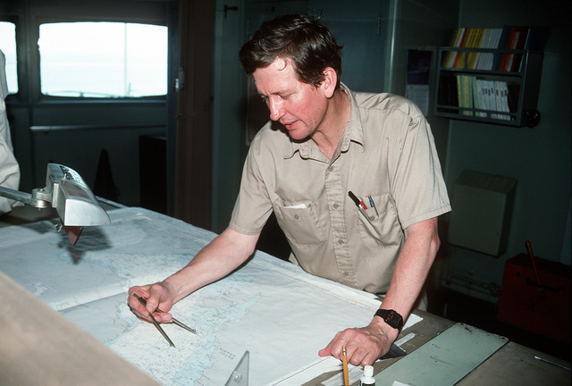 A crew member aboard a Military Sealift Command vehicle cargo ship consults a chart as he plans redeployment operations. Military equipment and ordnance is being loaded at various ports for shipment to the United States in the aftermath of Operation Desert Storm