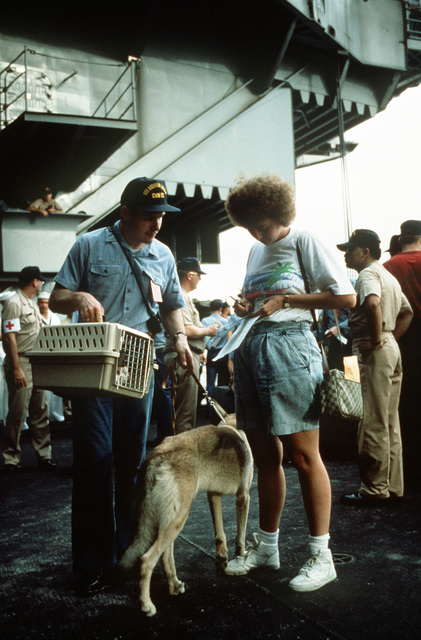 A military dependent fills out paperwork as she and her pets prepare to board the nuclear-powered aircraft carrier USS ABRAHAM LINCOLN (CVN-72). Dependents and non-essential military personnel area departing from the are in the aftermath of Mount Pinatubo's eruption. The volcano, which erupted for the first time in over 600 years, forced the U.S. military to coordinate Operation Fiery Vigil evacuation efforts to remove more than 20,000 evacuees from the area