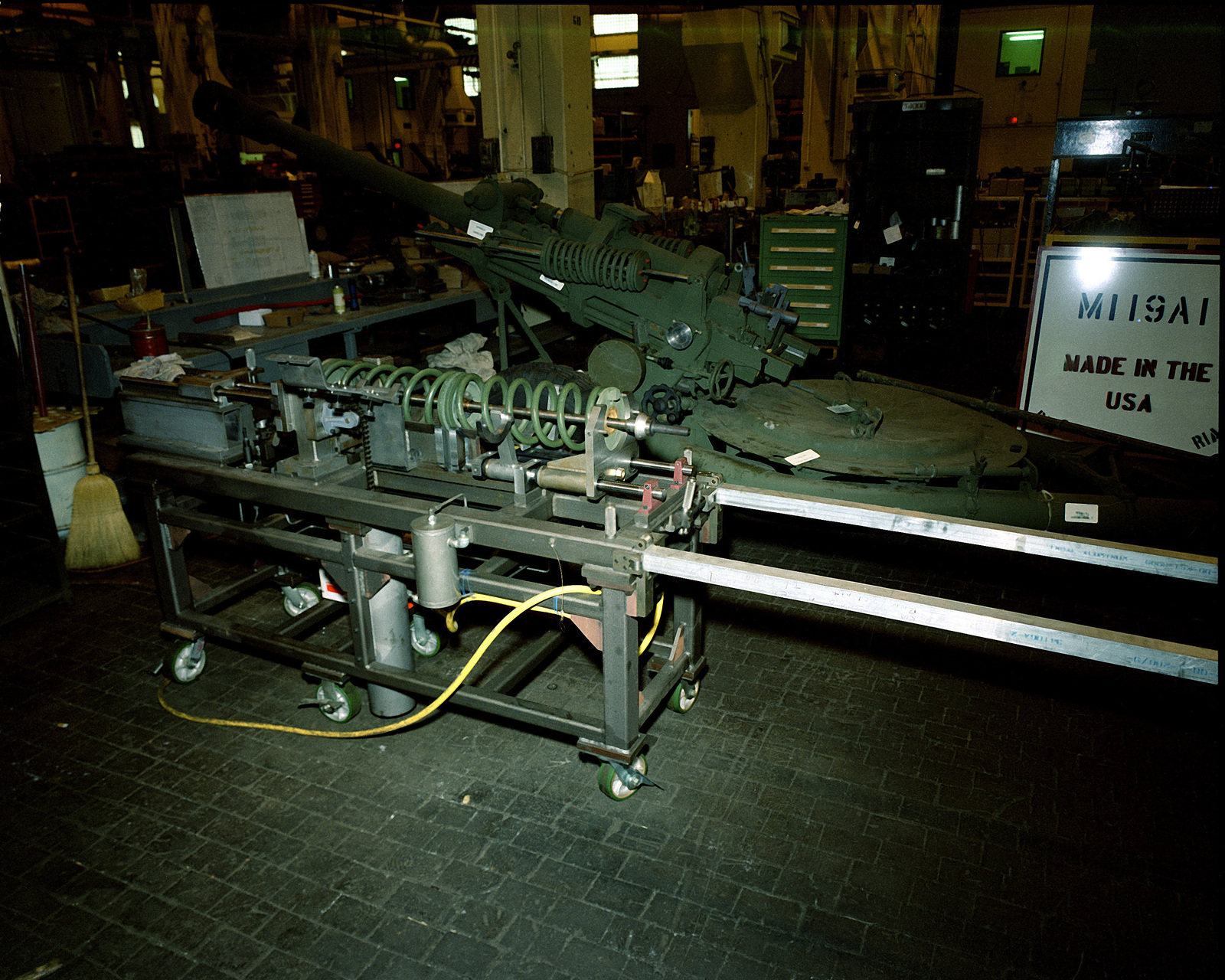 A spring compressor is used to assemble the balance gear of a 105mm M-119 light gun at the Rock Island Army Arsenal