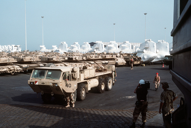 A video cameraman films an Oshkosh M-977 heavy expanded mobility tactical truck as it is readied for redeployment to the United States in the aftermath of Operation Desert Storm. M-1A1 Abrams main battle tanks, other armored vehicles and various helicopters wrapped for transport are parked in the holding area in the background