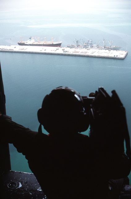 A video cameraman films loading operations from a helicopter as the Military Sealift Command-chartered freighter CAPE BON (T-AK-5059) and a merchant ship stand at pierside. The vessels are taking on equipment and ordnance for redeployment to the United States in the aftermath of Operation Desert Storm
