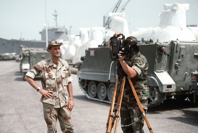 A video cameraman films military vehicles, equipment and ordnance being loaded aboard Military Sealift Command vehicle cargo ships for redeployment to the United States in the aftermath of Operation Desert Storm