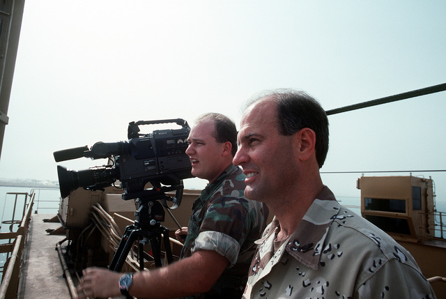 A video cameraman films operations as ordnance and equipment is loaded aboard Military Sealift Command vehicle cargo ships for redeployment to the United States in the aftermath of Operation Desert Storm