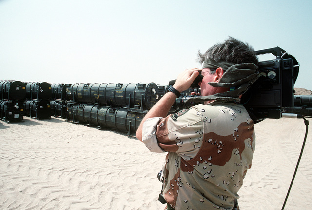 A video cameraman films ordnance containers at Ammo Supply Point 3 near Mishab. Ordnance and equipment are being loaded aboard Military Sealift Command vehicle cargo ships for shipment back to the United States in the aftermath of Operation Desert Storm