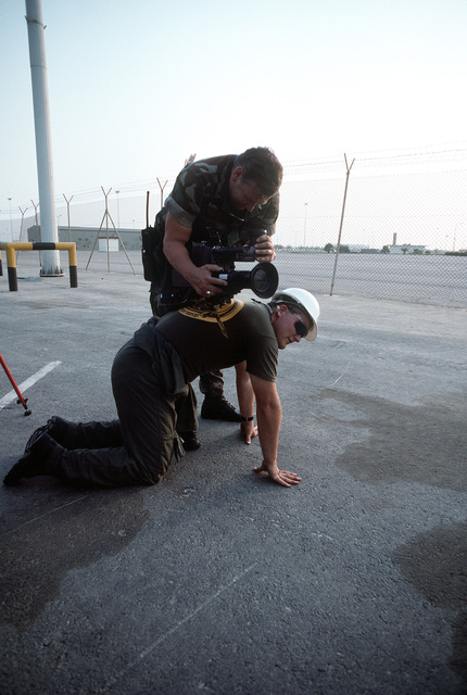 A video cameraman stabilizes his camera on a colleague's back as he prepares to film loading operations on a pier. Equipment and ordnance are being loaded aboard Military Sealift Command vehicle cargo ships for redeployment to the United States in the aftermath of Operation Desert Storm
