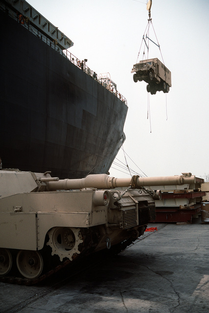 An M-935 5-ton van is lifted by crane from a pier in preparation for loading aboard a Military Sealift Command vehicle cargo ship as an M-1A1 Abrams main battle tank stands on the pier. Vehicles, equipment and ordnance are being loaded aboard ships for redeployment to the United States in the aftermath of Operation Desert Storm