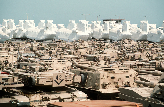 M-1A1 Abrams main battle tanks and protectively wrapped CH-47 Chinook helicopters cover a holding area in preparation for redeployment to the United States in the aftermath of Operation Desert Storm