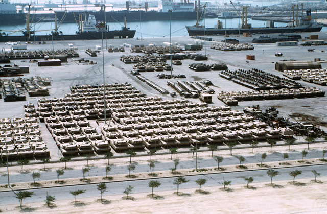 M-1A1 Abrams main battle tanks, foreground, and other armoured vehicles line a pier in preparation for redeployment to the United States in the aftermath of Operation Desert Storm