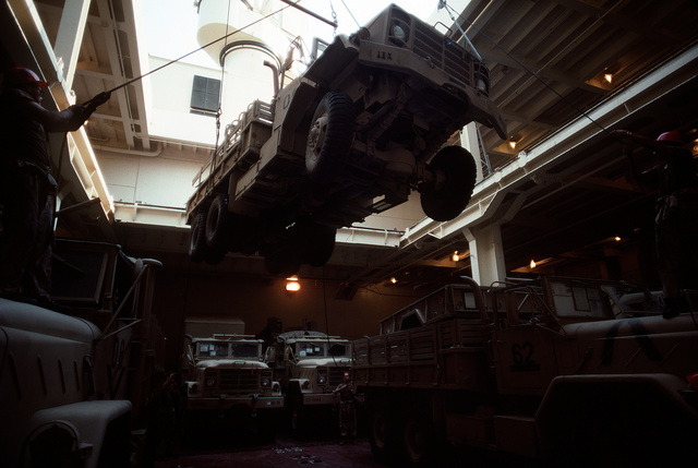 M-939A2 5-ton cargo trucks are loaded into the cargo hold of a vehicle cargo ship for redeployment to the United States in the aftermath of Operation Desert Storm