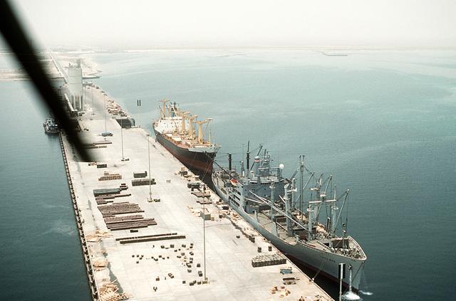 The Military Sealift Command-chartered freighter CAPE BON (T-AK-5059) stands at pierside with cargo holds open. The vessel will be taking on equipment and ordnance for redeployment to the United States in the aftermath of Operation Desert Storm. A merchant ship is docked behind the CAPE BON