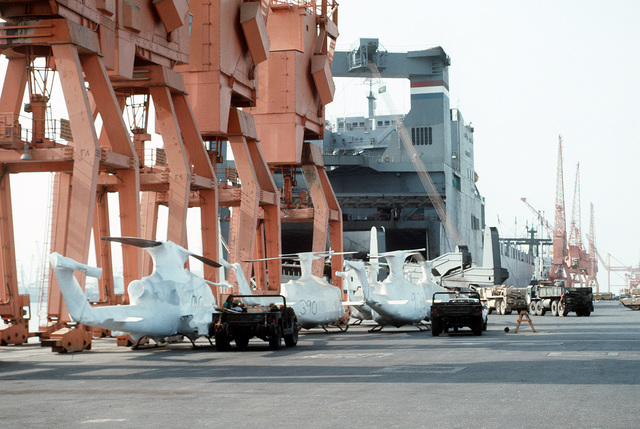 UH-1 Iroquois helicopters and AH-1 Cobra gunships wrapped in protective covering stand on the deck of a Military Sealift Command vehicle cargo ship in preparation for redeployment to the United States in the aftermath of Operation Desert Storm