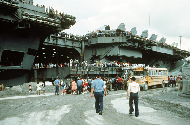 U.S. military dependents board the nuclear-powered aircraft carrier USS ABRAHAM LINCOLN (CVN-72) as they prepare to depart in the aftermath of Mount Pinatubo's eruption. The volcano, which erupted for the first time in over 600 years, forced the U.S. military to coordinate Operation Fiery Vigil evacuation efforts to remove more than 20,000 evacuees from the area