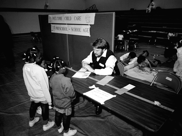 A volunteer checks paperwork as children stand by at a preschool facility set up for children evacuated from Subic Bay Naval Station and Clark Air Base, Philippines. Children and their familes, both military and civilian, were evacuated following the eruption of Mount Pinatubo, a volcano that came alive on June 10 for the first time in over 600 years. More than 20,000 evacuees have been removed from the area as part of the U.S. military's Operation Fiery Vigil