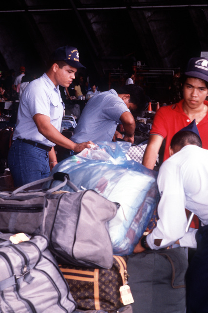 Navy baggage handlers process through customs the luggage of evacuees arriving with military and civilian personnel from the Philippine Islands after the June 10 eruption of Mount Pinatubo deposited more than four inches of volcanic ash on the area, disrupting base operations. More than 20,000 evacuees have been removed as a part of the U.S. military's Operation Fiery Vigil