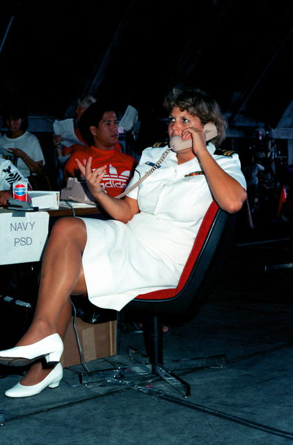 A Navy lieutenant talks on the telephone while working in a temporary evacuation center during Operation Fiery Vigil. The center was set up to process military dependents who were evacuated from the Philippines after volcanic ash from the eruption of Mount Pinatubo disrupted operations at Clark Air Base and Naval Station, Subic Bay.