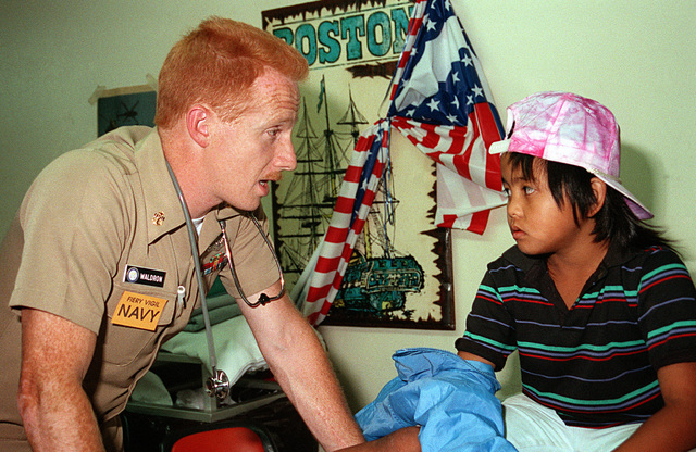 CHIEF Hospital Corpsman Dirk Waldron reassures a child in a medical treatment center set up for evacuees from Naval Station, Subic Bay and Naval Air Station, Cubi Point. The evacuation is taking place as part of Operation Fiery Vigil, an effort to remove civilian and military personnel and their dependents from the Philippines in the aftermath of Mount Pinatubo's eruption on June 10th.