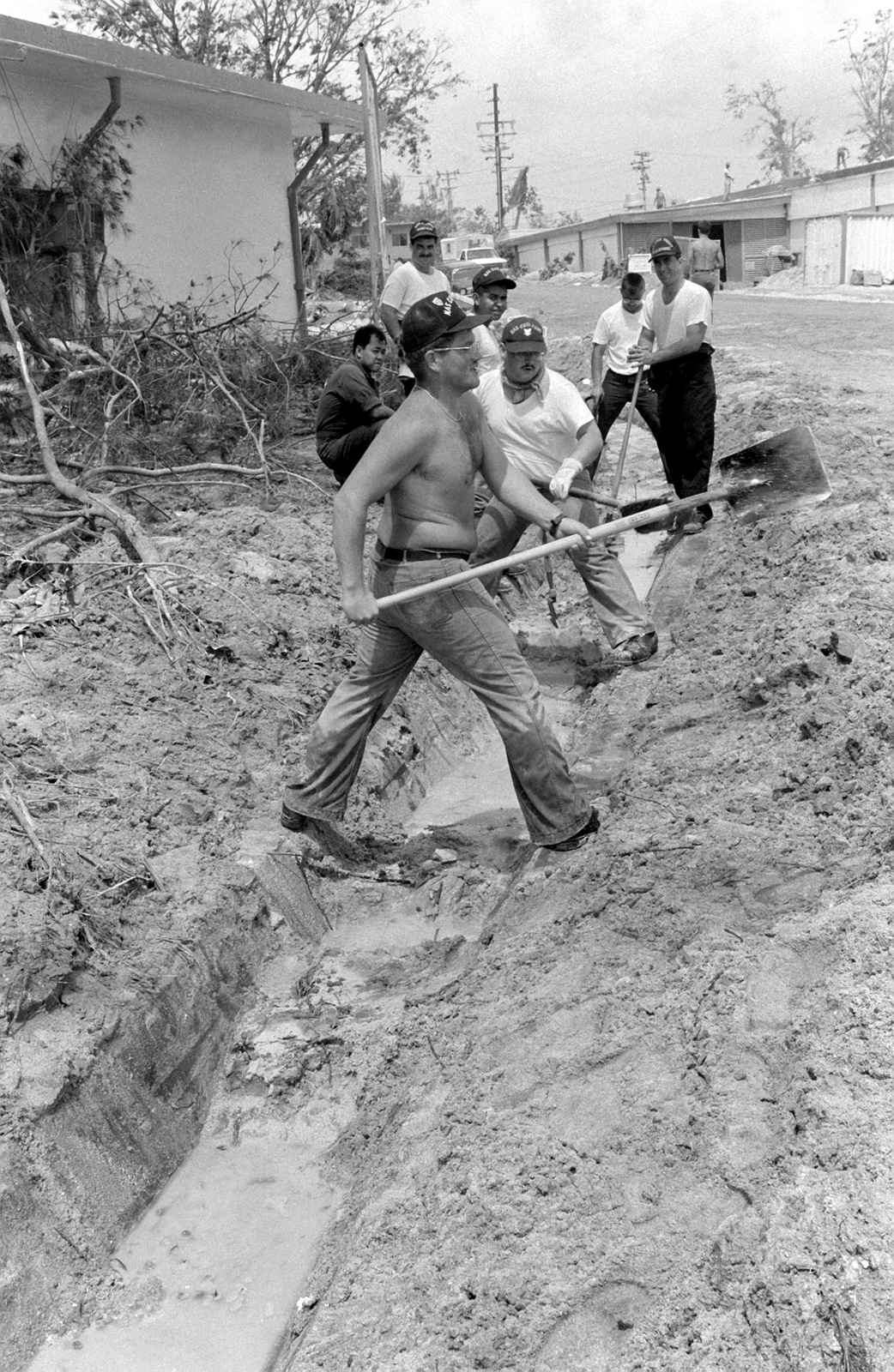 Personnel from the station dig a trench through ash in the