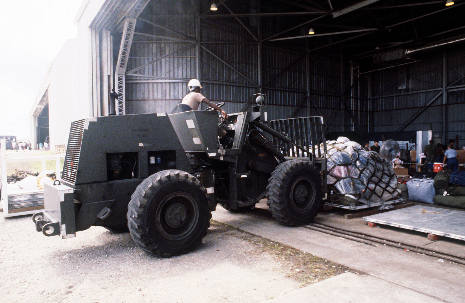 A US Air Force M220BFL rough terrain fork lift moves a pallet of luggage of evacuees from the Philippine Islands. The evacuation is the result of the June 10 eruption of Mount Pinatubo, which deposited more than four inches of volcanic ash on the Islands. More than 20,000 evacuees have been removed from the area as a part of the US military's Operation Fiery Vigil