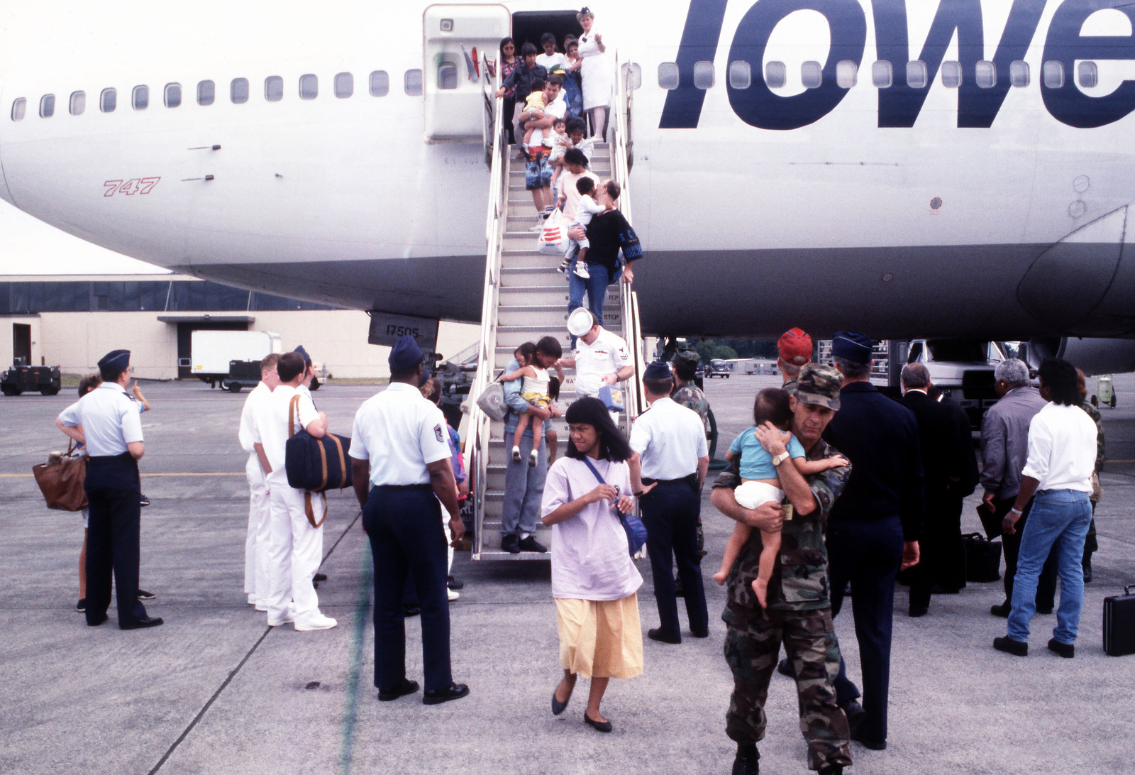 Service personnel assist dependents as they disembark from a chartered airliner upon their arrival at the base. The dependents were evacuated from Clark Air Base and Naval Station, Subic Bay, in the Philippines following the eruption of Mount Pinatubo