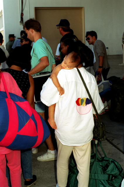 A mother carries her sleeping child as she and other evacuees from bases in the Philippines congregate in the base gym while stopping over en route to the United States. Civilian and military personnel and their dependents have been evacuated from Naval Station, Subic Bay and Naval Air Station, Cubi Point as part of Operation Fiery Vigil in the aftermath of Mount Pinatubo's eruption on June 10th.